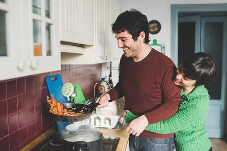 parejas romanticas: Half length of young handsome caucasian man and woman couple cooking together, she is hugging him form back and he is tossing a pan with vegetables - cooking, food, love concept Foto de archivo