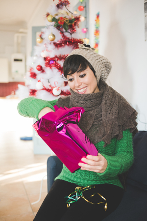unwrapping: Young handsome caucasian brown short hair woman sitting on the sofa in her apartment, unwrapping a christmas present - gift, surprise, christmas concept