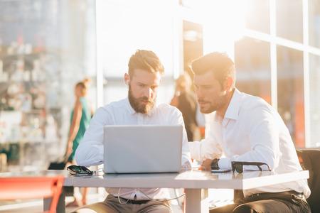 hombres jovenes: Dos jóvenes con barba caucásico moderno hombre de negocios sentado en un bar, con smartphone y un ordenador portátil, mirando hacia abajo la pantalla, sonriendo - negocio, trabajo, concepto de la tecnología