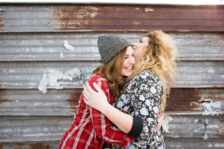 two and a half: Half length of two young curly and straight blonde hair caucasian woman hugging, smiling and having fun together - carefreeness, youthful, friendship, concept