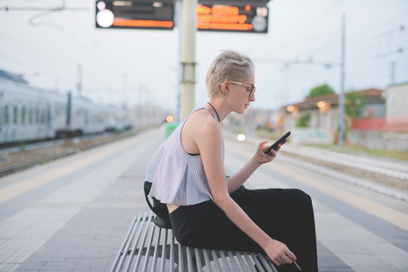 young handsome caucasian blonde italian designer sitting on a bench in railway station, using smartphone and smoking, looking downward, tapping the screen - technology, social network, travel concept