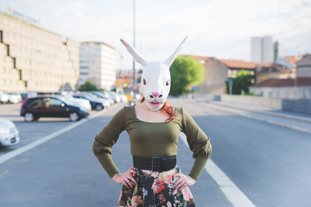 pin up: Half length of a young handsome caucasian redhead woman with rabbit mask, posing in the street of the city, hands on her hips - absurd, strange, dreamlike concept Stock Photo