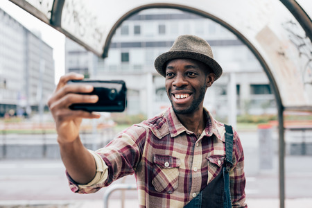 italian man: Half length of a young handsome afro black man holding a smartphone, taking a selfie, smiling - social network, vanity, technology concept Stock Photo