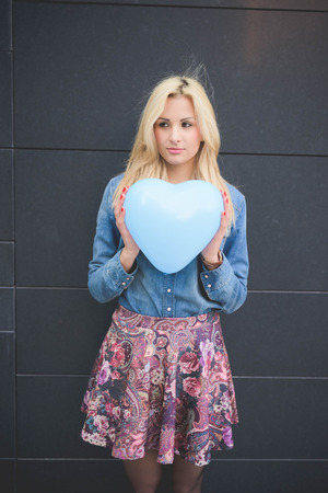hearted: Knee figure of young beautiful blonde girl posing leaning on a wall with a hearted balloon outdoor in the city overlooking right wearing a jeans shirt, a hat, and a floral skirt