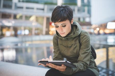 통신: 기술, 소셜 네트워크, 통신 개념 - 젊은 잘 생긴 백인 갈색 스트레이트 머리 여자, 도시 황혼에 앉아 태블릿을 들고, 아래로 화면을 찾고, 얼굴이 화면