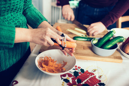 Close up on the hands of young handsome caucasian woman peeling carrots for dinner, man cutting vegetables too on the background - healthy, veggie, food concept