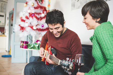 gitara: Połowa długość młody przystojny mężczyzna i kobieta para siedzi na kanapie, on gra na gitarze, ona patrzy na niego ze śmiechem - muzyka, święta, odpocząć koncepcję