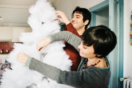familias unidas: Mitad de la longitud de la pareja de hombre joven caucásico hermoso y mujer montar el árbol de navidad, se centran en el hombre, sonriendo - navidad, día de fiesta, el concepto de invierno