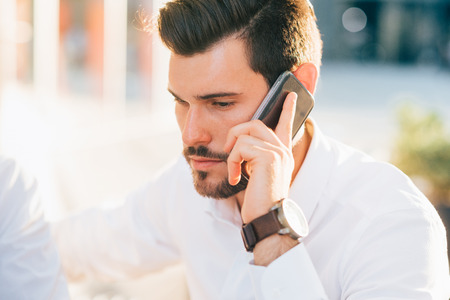 half length: Half length of young handsome black hair caucasian modern businessman talking smartphone in city backlight- business, working, communication concept