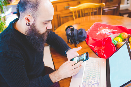 handhold: Young handsome caucasian bearded man sitting on a table using a smartphone handhold and a computer, looking down and tapping the screen - technology, work, multitasking concept Stock Photo