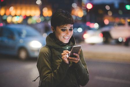 iluminado: Media longitud de la mujer caucásica joven marrón pelo lacio hermoso que sostiene un teléfono inteligente mirando hacia abajo de la pantalla en la ciudad de noche, la cara iluminada por ScreenLight - la tecnología, el concepto de comunicación