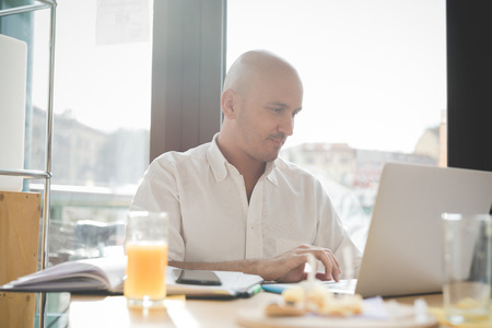 half dressed: Half length of young handsome caucasian bald business man sitting in a bar using a laptop looking downward and tapping the screen, smiling - working, happy, busy concept Stock Photo
