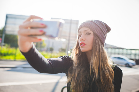 half length: Half length of young handsome caucasian blonde hair woman wearing hat taking selfie with smartphone handhold - vanity, technology, social network concept Stock Photo