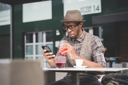 hombres de negro: joven negro afro hermoso que se sienta en una mesa y asidero teléfono inteligente, mirando hacia abajo la pantalla, bebiendo un jugo - la tecnología, la red social, el concepto de comunicación