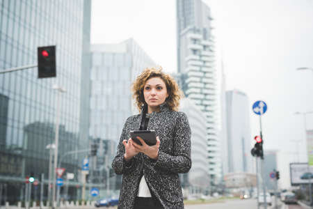 half length: Half length of a young beautiful caucasian contemporary businesswoman walking through the streets of the city using a tablet overlooking - technology, network, business, finance concepts