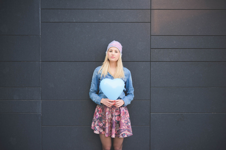 hearted: Knee figure of young beautiful blonde girl posing leaning on a wall with a hearted balloon outdoor in the city looking in camera wearing a jeans shirt, a hat, and a floral skirt