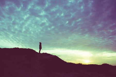 silueta de la luz trasera de un hombre de pie sobre una colina, con vistas, la vendimia se filtró - futuro, el poder, el concepto de logro
