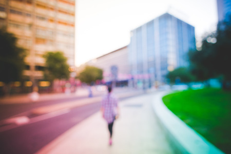 Intentionally blurred colorful filtered vintage view of a person walking alone in the street of a metropolis