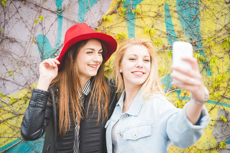 girls having fun: Half length of two young beautiful blonde and brunette girls having fun in the city taking selfie with smartphone handhold - technology, vanity, social network concept Stock Photo