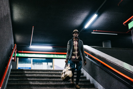 easy going: Young handsome afro black man going downstairs in the underground, holding a bag, overlooking left - youth, transport concept Stock Photo