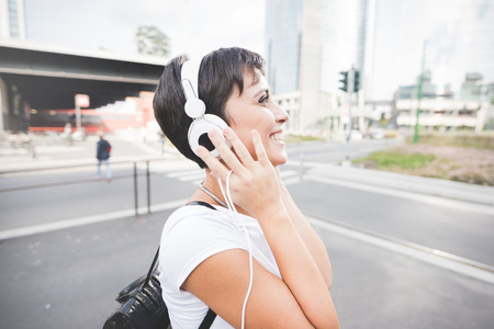half length: Half length portrait of young handsome caucasian brown straight hair woman listening music with headphones and smartphone handheld, overlooking left, smiling - music, relax, technology concept Stock Photo