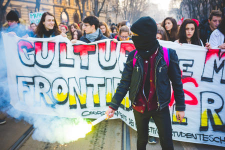 fascism: MILAN, ITALY - JANUARY 29: students demonstrating against racism, fascism and the meeting between Marie Le Pen and Matteo Salvini on Milan on January 29, 2016. A masked student holding a smoke pot. Editorial
