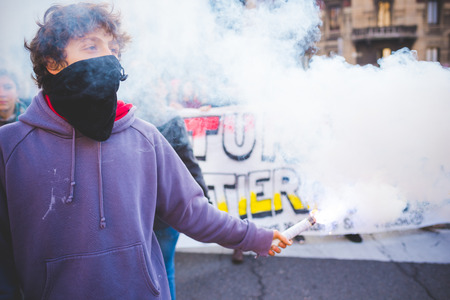 demonstrator: MILAN, ITALY - JANUARY 29: students demonstrating against racism, fascism and the meeting between Marie Le Pen and Matteo Salvini on Milan on January 29, 2016. A masked student holding a smoke pot. Editorial