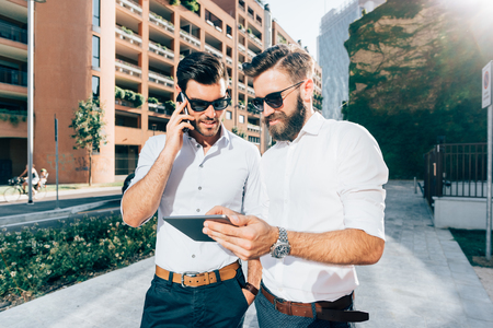 busy beard: Knee figure of two handsome bearded business man outdoor in the city, one talking smart phone, the other using a tablet hand hold - business, start up, finance, technology concept