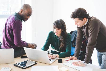 personas trabajando: la gente de negocios contemporáneos multirraciales que trabajan conectados con los dispositivos tecnológicos, como la tableta y el ordenador portátil, hablando juntos - finanzas, negocios, concepto de la tecnología