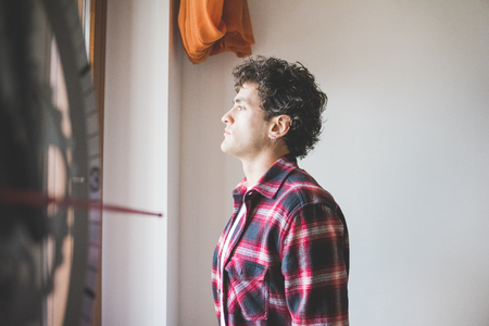 half length: Half length of young handsome lambersexual man standing near a window, overlooking, serious - pensive, thoughtful, thinking future concept Stock Photo