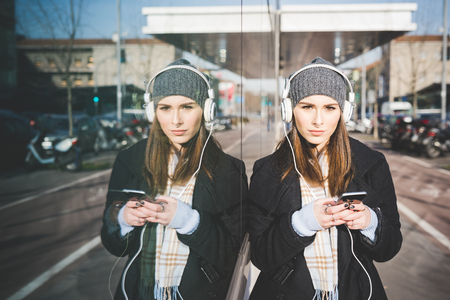 handhold: Half length of young beautiful caucasian woman listening music with headphones and smartphone handhold, looking in camera, leaning on a reflected surface wall - music, technology, reflection concept
