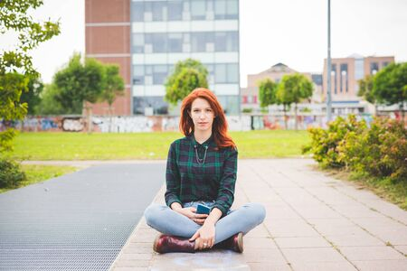leg: Young beautiful redhead woman sitting leg crossed in the city, holding a smartphone, looking in camera serene - technology, social network, serenity concept