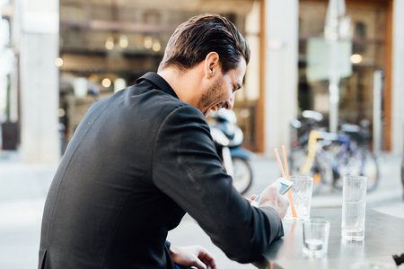 modern man: Rear view of young handsome man seated on a bar in the city center using a smartphone - social network, communication, technology concept Stock Photo