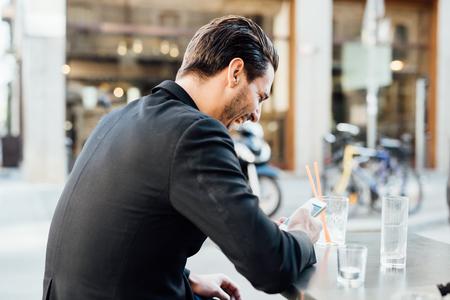 seated man: Vista trasera de un joven apuesto sentado en un bar en el centro de la ciudad utilizando un teléfono inteligente - red social, la comunicación, la tecnología concepto