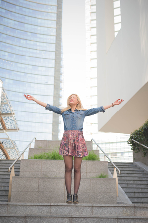 arms wide open: Young beautiful caucasian blonde girl posing on a staircase with arms wide open overlooking right dressed with floral skirt and jeans shirt - carefreeness, youth, freshness concept