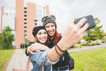 half length: Half length of two young handsome caucasian blonde and redhead hair women hugging outdoor in the city, holding smartphone, taking selfie, smiling - social network, communication, vanity concept