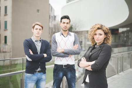 real leader: Multiracial business people working posing outdoor in the city, with ones arms folded, looking in camera, serious - seriousness, business, determination concept - focus on the woman Stock Photo
