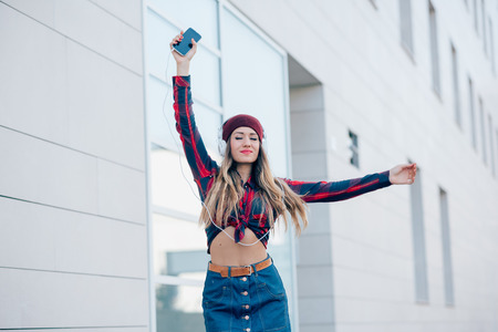 handhold: Knee figure of young handsome caucasian woman listening music with headphones and smartphone handhold feeling free with arms wide open - freedom, music, technology concept Stock Photo