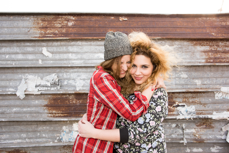 half length: Half length of two young curly and straight blonde hair caucasian woman hugging, smiling and having fun together - carefree, youthful, friendship, concept Stock Photo