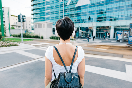 half length: Half length rear view of a caucasian woman with backpack listening music with headphones - music, relax concept