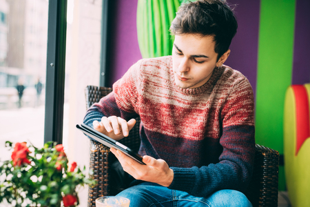 held down: Young handsome caucasian man sitting in a bar, holding a tablet, looking down and tapping the screen - social network, technology, communication concept