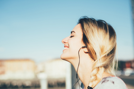 Profile portrait of young beautiful caucasian woman listening music with earphones, eyes closed, smiling - music, relaxing, serenity concept Stock Photo