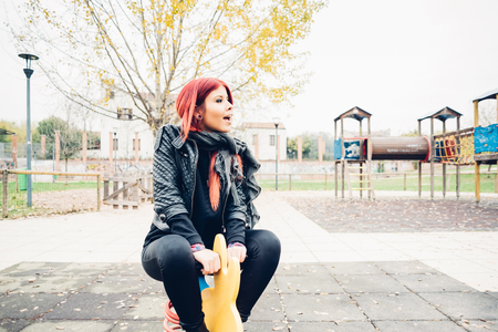 youthful: Young beautiful redhead hispanic woman playing in a playground in a park outdoor in the city - carefree, childhood, youthful concept Stock Photo