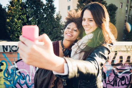 self conceit: Half length of a couple of young beautiful multiethnic women outdoor in the city back light holding a smart phone taking selfie - technology, vanity, social network concept