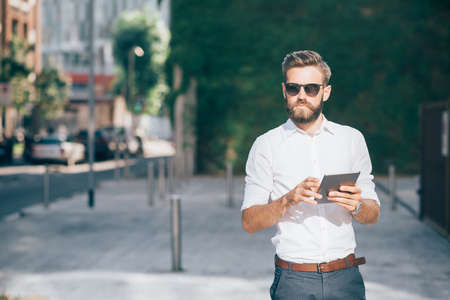 looking over: Knee figure of young handsome bearded businessman holding a tablet, looking over wearing sunglasses - technology, business, work concept, copy space left