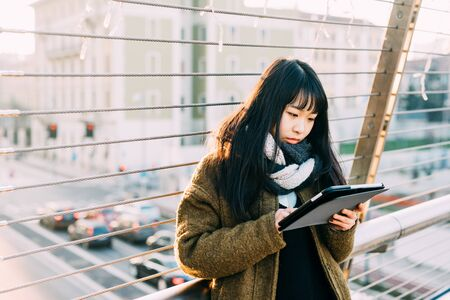 half length: Half length of young beautiful asiatic woman holding a tablet, looking down and tapping the screen - technology, social network, communication concept