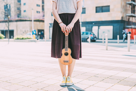 waist down: Detail from the waist down of a young woman holding an ukulele outdoor in the city - musician, composer concept Stock Photo