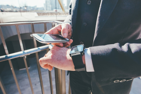 handhold: From the neck down view of businessman using smart watch and smart phone handhold - technology, business, communication concept Stock Photo