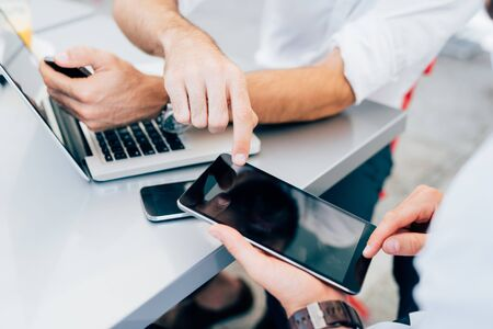 tapping: Close up on the hands of two men using technological devices, tapping the screen of a tablet hand hold - technology, communication, multitasking concept Stock Photo