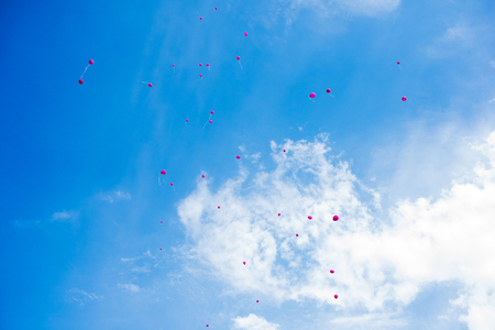 Pink balloon flying in blue sky